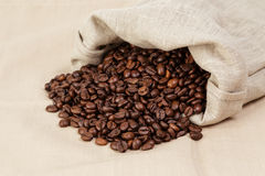 Roated coffee beans spill out of the bag Stock Photo