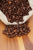 Roated coffee beans spill out of the bag Royalty Free Stock Photography