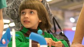 Robótica y niño educación, niños, tecnología, ciencia y concepto de la gente El niño pequeño lindo mira el electrónico metrajes