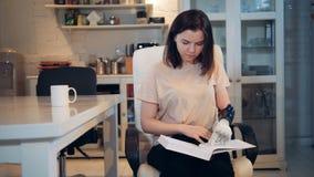 Robótico real humano-como o braço Uma senhora com um braço protético abre um livro