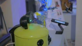 Robô amarelo engraçado da cubeta na exposição da tecnologia filme