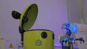 Robô amarelo engraçado da cubeta que tenta travar a mão da mulher na exposição da tecnologia filme