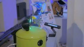 Robô amarelo engraçado da cubeta que tenta travar a mão da mulher na exposição da tecnologia video estoque