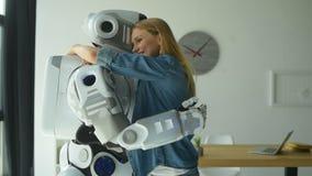 Robô amigável e jovem mulher que abraçam-se vídeos de arquivo
