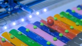 Robô que joga no xilofone colorido imagem de stock