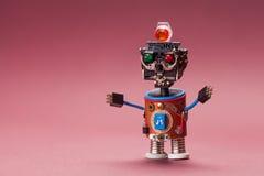 Robô retro do estilo Brinque o caráter com cabeça plástica preta, lâmpada verde colorida dos olhos do vermelho, mãos azuis do fio Imagens de Stock Royalty Free