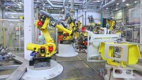 Robôs e trabalhador em uma fábrica do carro video estoque