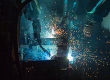 Robôs que soldam em uma fábrica do carro Imagem de Stock