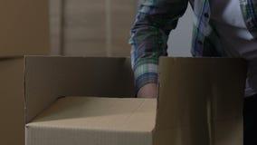 Roba dell'imballaggio dell'uomo nel cartone, divorzio, divisione della proprietà, muoventesi dalla casa archivi video
