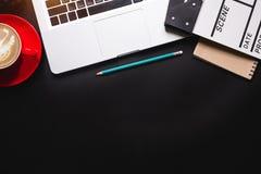 Roba dell'ufficio con il computer portatile della valvola di film e la tazza di caffè immagini stock libere da diritti