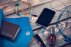 Roba della borsa di signora, Smart Phone, cuffie dell'orecchio, cosmetici, gioielli Fotografia Stock