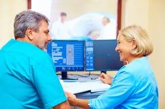 Roba medica adulta con esperienza che parla della diagnosi paziente nella stanza di tomografia Immagine Stock