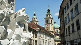 Ljubljana, Slovenia - 07/17/2015 - Robba Fountain and Ljubljana Cathedral, sunny day royalty free stock images