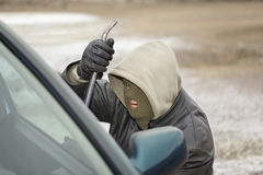 Robber. Trying to break open the car door Royalty Free Stock Photo