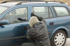 Robber. With a crowbar trying to open the car door Royalty Free Stock Photo