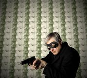 Robber. A robber pointing a gun with a banknotes background Royalty Free Stock Photo