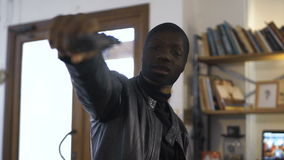 The robber aiming with the gun. The blurred African robber aiming with the gun to the camera