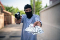 Robber aiming a gun to taking money from victim tourist on the w Stock Photo