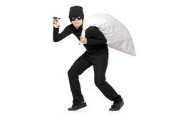 Robber with a bag and flashlight in hands. Isolated against white background Royalty Free Stock Photo