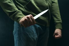 A robber with a big knife - a sharp-assassin murderer about to commit murder, robbery, theft. News articles, newspaper, social. Advertising stock photos