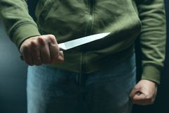 A robber with a big knife - a sharp-assassin murderer about to commit murder, robbery, theft. News articles, newspaper, social. Advertising stock image