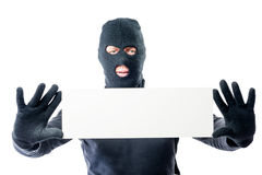 Robber in black clothes and mask with a poster in hands. On a white background Royalty Free Stock Photo