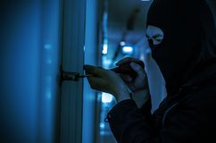 Robber with black tights over the head breaking the door lock. Low key. Selective focus Stock Image