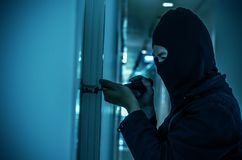 Robber with black tights over the head breaking the door lock. Black and white. Low key. Selective focus Royalty Free Stock Image