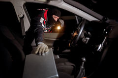 Robber breaking a car's  to steal a lap top Stock Images
