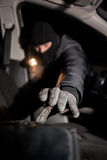 Robber breaking a car's windows to steal a  bag Royalty Free Stock Image