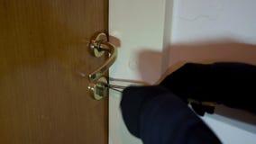 Robber breaking the door lock. Robber with black gloves breaking the door lock. Focus on the keyhole stock video