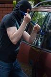 Robber breaks car window Royalty Free Stock Image