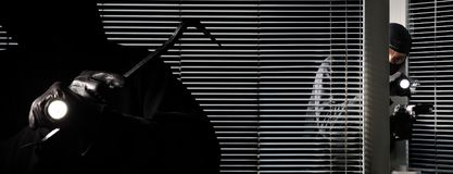 Robber burglar thieves are breaking into the house, with torch, crowbar and gun  in black door window. Robber burglar thieves are breaking into the house, with stock image