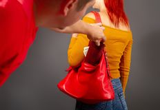 The thief steals from the bag. The robber comes up from the back to the girl secretly pulls out of her bag a purse with money royalty free stock photo