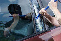 Robber with crowbar smashing glass Royalty Free Stock Photo