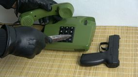 Robber gangster hand with black glove and dagger gun pressing numbers buttons on retro green telephone stock video footage