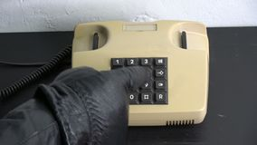 Robber gangster hand with black leather glove pressing numbers buttons on old telephone stock video