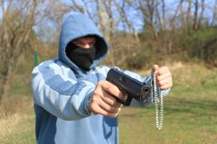 Robber with a gun. Assault with a weapon, a masked robber Stock Photos