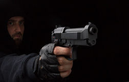 Robber with gun. Masked robber with gun against a black background Royalty Free Stock Photos