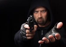Robber with gun holding out hand. Against a black background