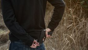Robber hide gun in back pocket royalty free stock photography