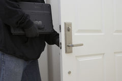 Robber Holding Laptop While Opening Door Of House Stock Photo