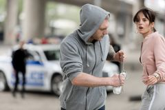 Robber in hoodie running with stolen handbag from shocked young. Woman stock photos