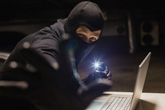 Robber looking at camera while making light with his phone Royalty Free Stock Images