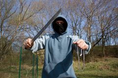Robber with a machete. Assault with a weapon, a masked robber Royalty Free Stock Photos