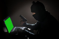 Robber man hacking computer and hold gun. Royalty Free Stock Photography