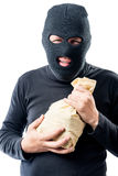 Robber in a mask with a bag of money on a white Stock Photos