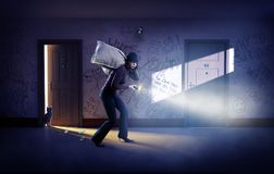 Robber in a mask with bags of money. Sings at the wall royalty free stock photo