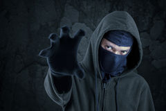 Robber with mask catching something Royalty Free Stock Images