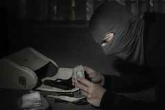Robber in a mask and with a flashlight examines the contents of the women`s bag in  room. Robber in a mask and with a flashlight examines the contents of the royalty free stock photography